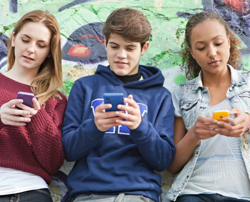 Teenagers using their smartphones simultaneously.